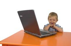 Un niño con una computadora portátil. Foto de archivo libre de regalías