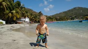 Un niño en una playa en las zonas tropicales Imagenes de archivo