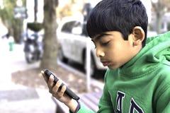 Un niño está mirando su teléfono elegante en una calle Imagen de archivo