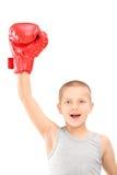 Un niño feliz con los guantes de boxeo rojos que gesticula triunfo Foto de archivo
