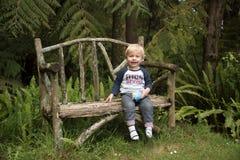 Un niño feliz que se sienta en un banco del jardín Fotografía de archivo