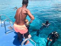 Un noir, plongeurs de aide d'homme sportif sportif basané et arabe dans les costumes noirs de plongée à l'air avec des bouteilles images stock