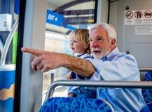 Un nonno passa il tempo di qualità con il suo nipote su un treno della ferrovia fotografie stock