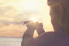 Un nouveau jour commence par le lever de soleil protégé dans les mains d'une femme Photos libres de droits