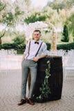 Un novio masculino joven hermoso en una camisa, una corbata de lazo, pantalones y ligas presenta al lado de un barril para el vin Fotos de archivo libres de regalías