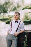 Un novio masculino joven hermoso en una camisa, una corbata de lazo, pantalones y ligas presenta al lado de un barril para el vin Fotografía de archivo