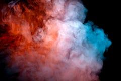 Un nuage dense et tourbillonnant de fumée colorée sur un fond noir, accentué en rouge et bleu dans les vagues du vape image stock