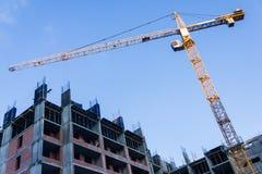 Un nuevo edificio se está construyendo con el uso grúa horca Fotografía de archivo libre de regalías
