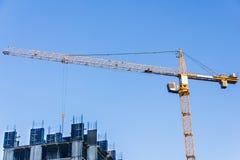 Un nuevo edificio se está construyendo con el uso grúa horca Imagen de archivo libre de regalías
