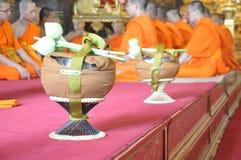 Un nuevo monje enciende incienso durante una ceremonia budista de la ordenación Imagen de archivo