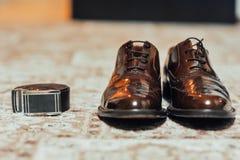 Un nuevo par de zapatos de cuero del moreno, correa imagenes de archivo