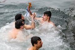 Un nuotatore bacia un incrocio di legno recuperato dal mare, durante Fotografie Stock Libere da Diritti
