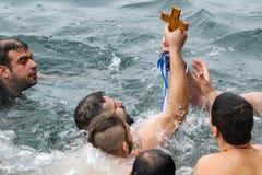 Un nuotatore bacia un incrocio di legno recuperato dal mare, durante Fotografia Stock Libera da Diritti
