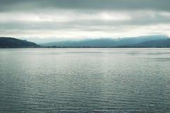 Un océan argenté calme, avec des montagnes à l'arrière-plan photos stock