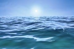 un océano azul con el sol sobre el horizonte libre illustration