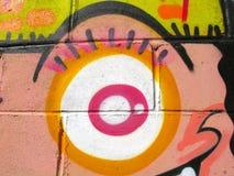 Un oeil étrange peint sur un fond de bloc de ciment Images libres de droits