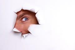 Un oeil curieux examine le trou déchiré sur une feuille blanche image stock