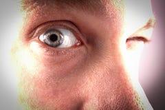 Un oeil regarde par une porte de trou photographie stock libre de droits