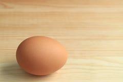 Un oeuf de poule cru frais d'isolement sur la table en bois, avec l'espace libre pour le texte et la conception Photo stock