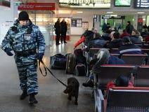 Un oficial de policía comprueba la sala de espera del ferrocarril con un perro del servicio Imagenes de archivo