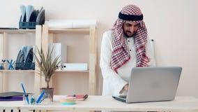Un oficinista árabe moderno trabaja en un ordenador portátil en la oficina Musulmanes vestidos en el traje nacional del ghutra kh almacen de metraje de vídeo