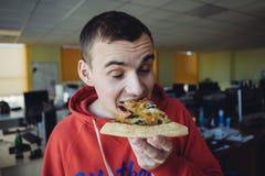 Un oficinista joven que come la pizza deliciosa contra un fondo del espacio de oficina Alimentos de preparación rápida una rotura Fotos de archivo libres de regalías