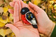 Un oiseau de jouet, une broche perlée faite main de bouvreuil, se trouvant sur les paumes des femmes Le fond est brouill? images libres de droits