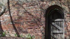 Un old-fashioned a arqué la porte en bois dans un mur de briques à St Albans, R-U banque de vidéos
