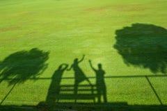 Un'ombra di tre gente ed alberi in erba verde Immagini Stock