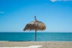 Un ombrello della paglia alla spiaggia con la sabbia perfetta e mare blu a Torremolinos fotografia stock libera da diritti
