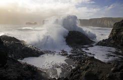 un'onda enorme dall'Oceano Atlantico copre la pietra vulcanica nera sulla banca nera della sabbia della lava in Islanda immagini stock libere da diritti