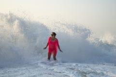 Un'ondata di due misurano le sorprese con un contatore una giovane donna sulla spiaggia Immagini Stock Libere da Diritti