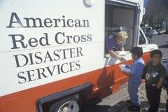 Un operaio della croce rossa che distribuisce i pasti Immagine Stock