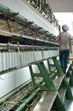 Un operaio femminile che lavora nel gruppo di lavoro della tessile Immagine Stock
