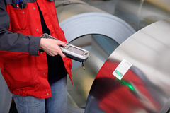 Un operaio ha scandetto la produzione del rullo d'acciaio Fotografia Stock
