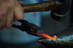 Un operaio metallurgico modella un pezzo di ferro 1 Fotografie Stock Libere da Diritti