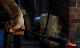 Un operaio metallurgico modella un pezzo di ferro 2 Fotografie Stock