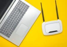 Un ordinateur portable et un routeur de Wi-Fi sur un fond de papier jaune Clavier, touchpad Technologies de Digitals modernes Cop photo stock