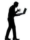 Un ordinateur portatif d'ordinateur de silhouette d'homme fâché Image stock