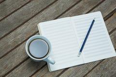 Un organizador abierto con la taza de café Foto de archivo libre de regalías