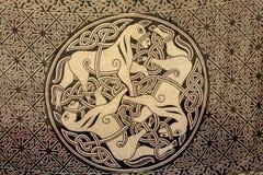 Un ornamento celtico di tre cavalli sul tessuto Simbolo antico di Immagine Stock