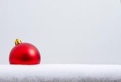 Un ornamento rojo de la Navidad en la nieve Fotos de archivo