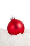 Un ornamento rojo de la Navidad en nieve foto de archivo
