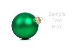 Un ornamento/una chuchería verdes de la Navidad en blanco Foto de archivo