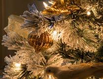 Un ornement cannelé de Noël d'or sur un arbre de Noël assemblé photo libre de droits