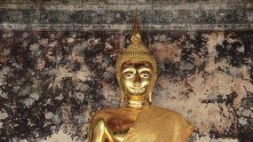 Un oro Buddhas con la cara de la misericordia y las paredes viejas fotos de archivo libres de regalías