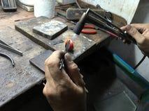 Un oro che fa il lavoratore sta infornando sull'anello di oro per regolare il suo si Fotografia Stock Libera da Diritti