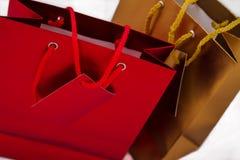 Un oro e una borsa rossa del regalo Fotografie Stock Libere da Diritti