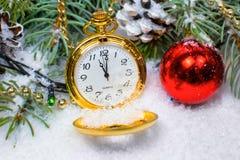 Un orologio d'annata nella neve contro lo sfondo di un albero di Natale e di una ghirlanda Fotografie Stock