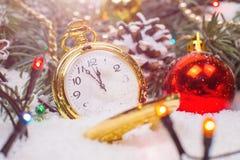 Un orologio d'annata nella neve contro lo sfondo di un albero di Natale e di una ghirlanda fotografia stock libera da diritti